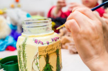 decoupage bottle. Professional painter paints a souvenir